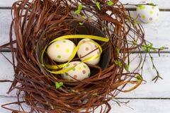 Wielkanocny tło z barwionymi jajkami w białych deskach i gniazdeczku Zdjęcie Stock