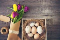 Wielkanocny tło z jajkami w gniazdeczku i tulipanach purpurowych i żółtych Zdjęcia Stock