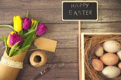 Wielkanocny tło z jajkami w gniazdeczku i tulipanach purpurowych i żółtych Fotografia Stock