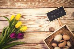 Wielkanocny tło z jajkami w gniazdeczku i tulipanach purpurowych i żółtych Obrazy Stock