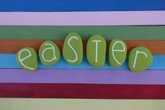 Wielkanocny tekst komponujący z zielenią barwił kamienie nad wielo- barwioną drewnianą deską ilustracja wektor