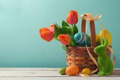 Wielkanocny wakacyjny kosz z jajkami, kwiatami i Wielkanocnym królikiem, Fotografia Royalty Free