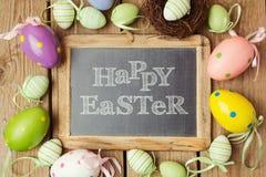 Wielkanocny wakacyjny pojęcie z jajka chalkboard na drewnianym tle i dekoracjami obraz stock