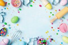 Wielkanocny wypiekowy tło z toczną szpilką, śmignięciem, dekoracyjnymi jajkami, ciastko krajaczami, cukierkiem i kolorowymi confe obraz stock