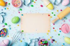Wielkanocny wypiekowy t?o z papierow? kart?, toczn? szpilk?, ?migni?ciem, dekoracyjnymi jajkami, ciastko krajaczami, cukierkiem i obraz royalty free