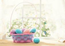 Wielkanocny zakupy temat: kolorowi jajka w koszu na okno w słonecznym dniu z motylami Fotografia Royalty Free