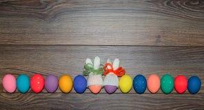 Wielkanocnych jajek ręka malował z trykotowymi królików kapeluszami nad drewnianym tłem z kopii przestrzenią wielkanoc szczęśliwy Fotografia Stock