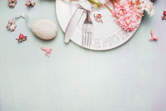 Wielkanocy granica z stołowym miejsca położeniem z wystrojów kwiatami i jajkiem na lekkim pastelowym drewnianym tle, odgórny wido fotografia stock