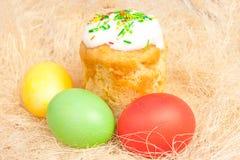 Wielkanocy jajka na jaskrawym i tort Obraz Royalty Free