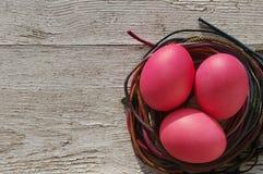 Wielkanocy różowi jajka w gniazdeczku z jaskrawymi taśmami Obraz Royalty Free