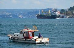 Wielki ładunku statek iść wzdłuż Bosphorus, mała łódź rybacka z rybakiem w przedpolu obrazy royalty free
