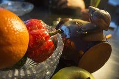Wielki ślimaczek gliniany garnek patrzeje krystaliczną wazę z dyniowym jabłkiem i mandarynem zdjęcia royalty free
