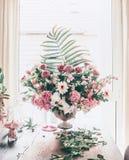 Wielki świąteczny klasyczny bukiet z różnorodnymi kwiatami i palmą opuszcza w łzawica wazie na stole przy okno w żywym pokoju obrazy royalty free