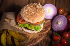 Wielki apetyczny hamburger z wołowiną, grulami i serem na drewnianej powierzchni, Zdjęcia Stock