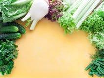 Wielki asortyment zielenie, sałata i warzywa na kolor żółty deski odgórnym widoku, Zdjęcie Stock