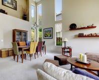 Wielki beżowy jaskrawy żywy pokój z jadalnia stołem z różnymi kolorów krzesłami Fotografia Stock