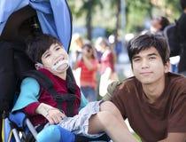 Wielki Brat bierze opiekę niepełnosprawny brat w wózku inwalidzkim Obrazy Stock