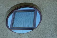 Wielki brown round okno na szarej betonowej ścianie budynek fotografia royalty free