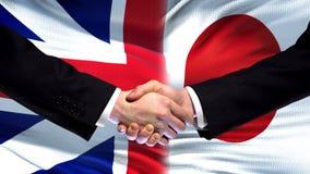 Wielki Brytania i Japonia uścisk dłoni, międzynarodowa przyjaźń, chorągwiany tło zdjęcie stock