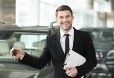 Wielki choise! Przystojna młoda klasyczna samochodowego sprzedawcy pozycja przy th Obraz Stock