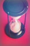 Wielki czarny hourglass przeciw czerwonemu tłu fotografia royalty free