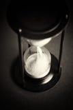 Wielki czarny hourglass przeciw czerwonemu tłu zdjęcie stock