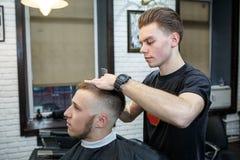 Wielki czas przy zakładem fryzjerskim Rozochocony młody brodaty mężczyzna dostaje ostrzyżenie fryzjerem podczas gdy siedzący w kr Zdjęcie Royalty Free