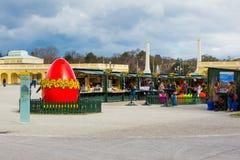 Wielki czerwony jajko przy wielkanoc rynkiem w Wiedeń i ludzie chodzi wokoło Obraz Royalty Free