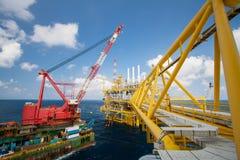 Wielki dźwigowy naczynie instaluje platformę w na morzu, dźwigowej barce robi żołnierza piechoty morskiej dźwignięcia ciężkiej ins Zdjęcie Stock