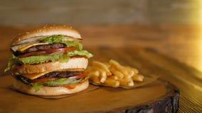 Wielki dwoisty hamburger kłama na drewnianej desce obok francuskich dłoniaków Profesjonalnie gotujący fast food zdjęcie wideo