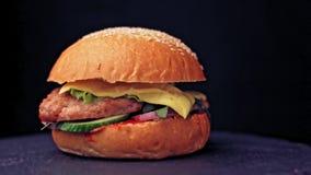 Wielki hamburger z cutlet, pomidorami, pieczarkami i ogórkami z rozciekłym serem wołowiny, wiruje na drewnianej desce na ciemnym  zbiory wideo