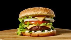 Wielki hamburger z cutlet, pomidorami, pieczarkami i ogórkami z rozciekłym serem wołowiny, wiruje na drewnianej desce na czerni zbiory wideo