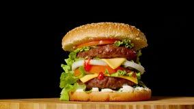 Wielki hamburger z cutlet, pomidorami, pieczarkami i ogórkami z rozciekłym serem wołowiny, wiruje na drewnianej desce na czerni zdjęcie wideo