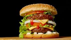 Wielki hamburger z cutlet, pomidorami, pieczarkami i ogórkami z rozciekłym serem wołowiny, wiruje na drewnianej desce na czerni zbiory