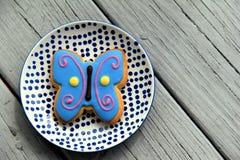 Wielki motyli ciastko frosted w jaskrawych kolorach, set na ładnym talerzu Obrazy Royalty Free