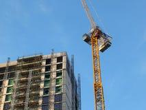 Wielki nowożytny budynku w budowie zakrywający w rusztowaniu z basztowym żurawiem przeciw jaskrawemu niebieskiemu niebu fotografia stock