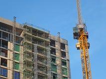 Wielki nowo?ytny budynku w budowie zakrywaj?cy w rusztowaniu z basztowym ?urawiem przeciw jaskrawemu niebieskiemu niebu obrazy stock