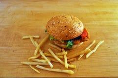 Wielki soczysty hamburger - babeczka z adra, francuz smaży zdjęcie stock