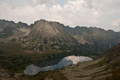 Wielki Staw Polski lake in Tatry mountains with peaks and clouds reflextion. Lake called Wielki Staw Polski in Dolina Pieciu Stawow Polskich in polish part of stock photography