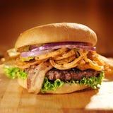 Wielki wyśmienity hamburger z smażyć cebulkowymi słoma. Obrazy Stock
