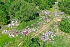 Wielki wysypisko śmieci, gospodarstwo domowe odpady, klingeryty i inne rzeczy wśród zielonego lasu wzdłuż łąk i drogi zdjęcie royalty free