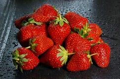 wielkie dojrzałe czerwone truskawkowe jagody na ciemnym tle nawadniają dro Zdjęcia Stock