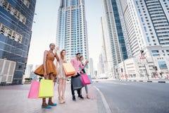 wielkie zakupy Cztery przyjaciela trzyma torba na zakupy w ich ręce Fotografia Royalty Free