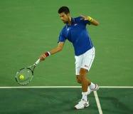 Wielkiego Szlema mistrz Novak Djokovic Serbia w akci podczas mężczyzna ` s przerzedże pierwszy round dopasowanie Rio 2016 olimpia Fotografia Royalty Free