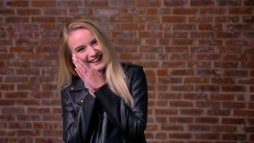 Wielkiej roześmianej blondynki caucasian kobieta jest trwanie, patrzejąca kamerę i pokazywać energiczną emocję na jej twarzy