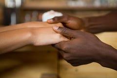 Wielo- etniczne pary mienia ręki w kawa domu Zdjęcie Stock