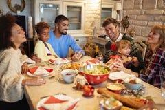 Wielo- etniczni przyjaciele zabawę przy rodzinnym Bożenarodzeniowym gościem restauracji zdjęcie royalty free
