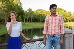 Wielo- etniczny pary główkowanie podczas gdy patrzejący smutny na moście zdjęcie royalty free
