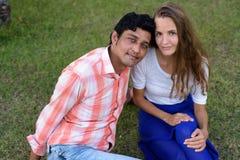 Wielo- etniczny pary obsiadanie na łące w miłości przy pokojowym gr zdjęcia royalty free