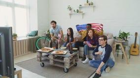 Wielo- grupa etnicza przyjaciele ogląda sporta mistrzostwo na TV wpólnie rozwesela w górę ich z usa flaga państowowa zbiory wideo